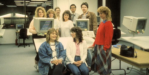 Some of the UGSL Vernon conversion centre staff posing around an IBM GFIS workstation.