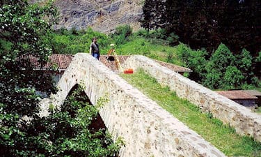 C. Cryderman setting up a GPS basestation atop an old stone bridge near Amurrio, Spain. Underhill was providing GPS equipment and processing to MWH Geo-Surveys on their gravity survey for the Basque Oil Company, 1996.