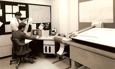 J.M. Parnell, and D. Turner (programmer), at the Wang WCS/20. The Wang had 32Kb of memory, and dual 250Kb floppy drives (one for the software, and one for data). Survey/plotting software (TRIAX) was developed in-house. ca. 1975-1985.