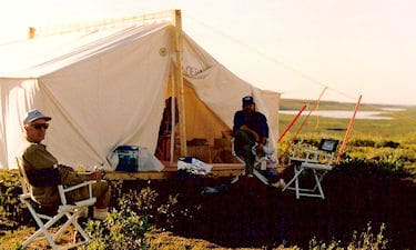 "W.G. Robinson and G.C. Friesen, at the Horton River camp, on the Inuvialuit Land Claim Boundary survey, 1988. The sign on the cook/calculation tent is the ""Underhilton"". A play on words by Sunrise Helicopters who supplied the camp."
