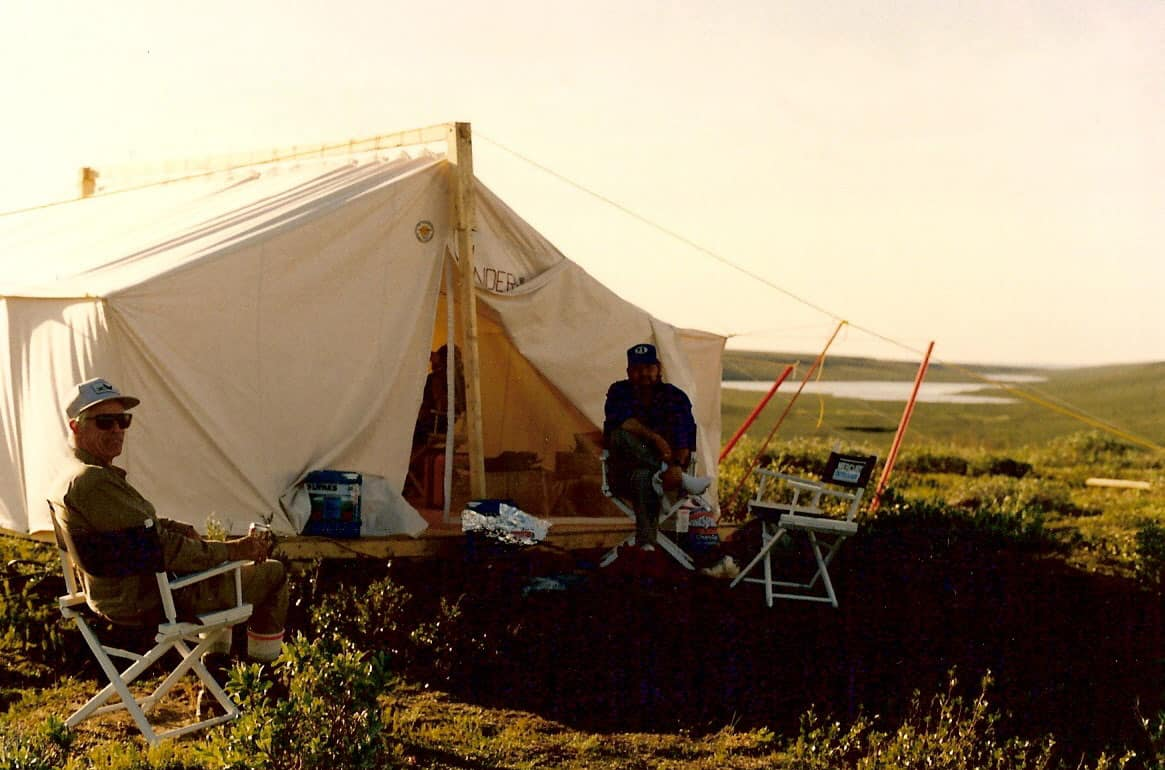 "W.G. Robinson and G.C. Friesen on the Inuvialut Land Claim Boundary survey, 1988. The sign on the cook/calculation tent is the ""Underhilton"". A play on words by Sunrise Helicopters who supplied the camp."