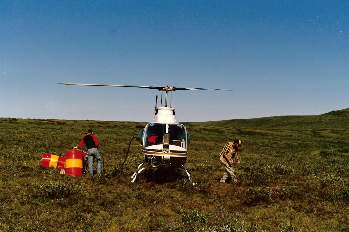 On the Inuvialuit Land Claim Boundary - near Horton River, NT. G.C. Friesen loading up the helicopter, 1988.