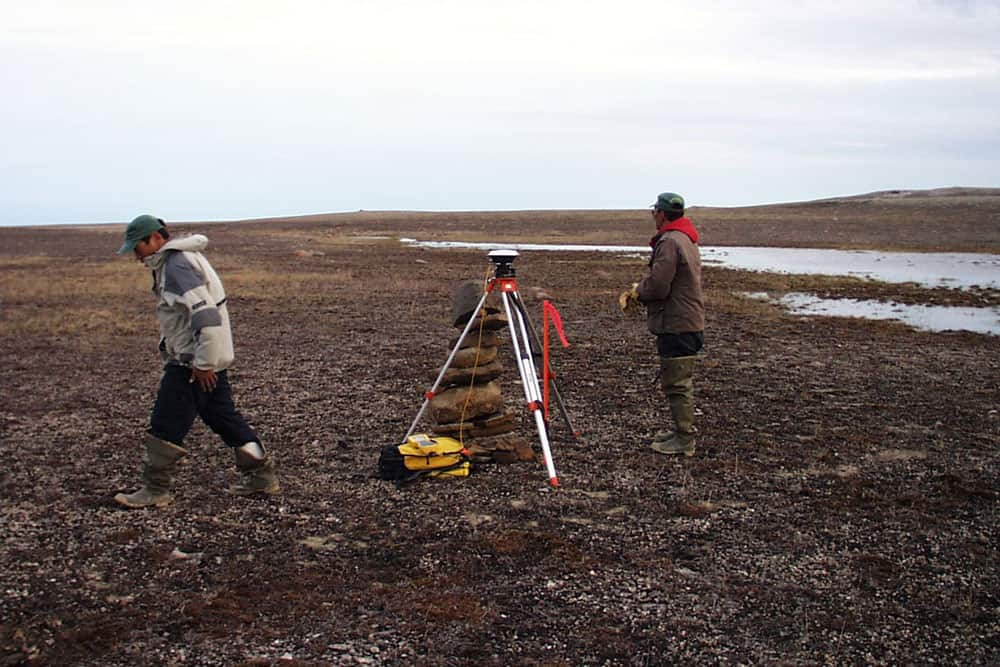 Assistants finishing up at boundary corner on Nunavut Land Claims. Taloyoak, 2000.