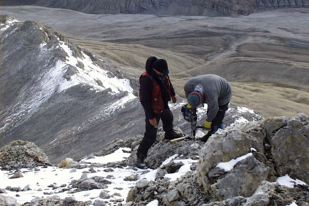 T. Connolly and J.C. settinf a rock post at a height of land, Ellismere Island, NU, 1998.