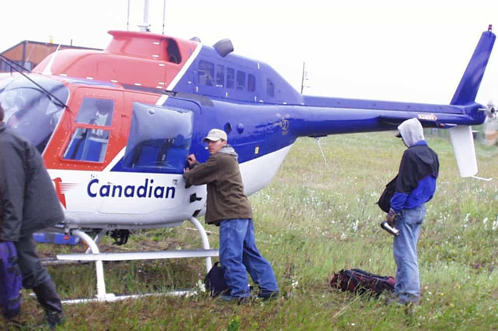 Assistants loading the helicopter for Sahtu Land Claim survey. Tulita, 1999.